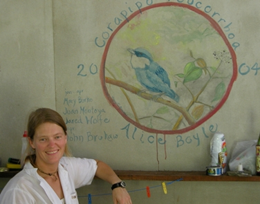 Mary with mural of White-ruffed Manakin, painted in cabin in Braulio Carrillo National Park